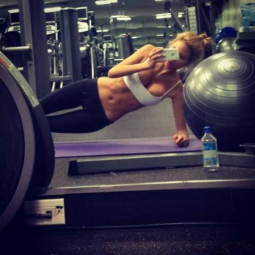 fit woman making photo while doing a plank