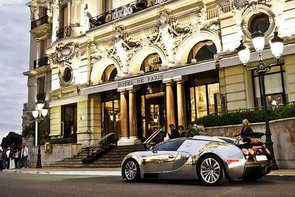 hotel de paris with a car next to it